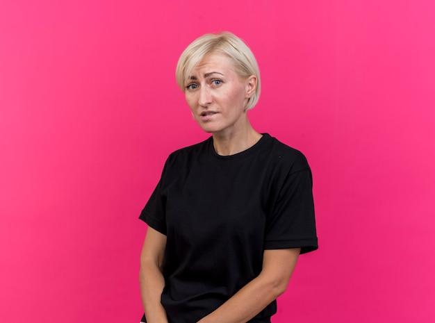 Niespokojna blond słowiańska kobieta w średnim wieku gryzie wargę na białym tle na szkarłatnej ścianie z miejsca na kopię