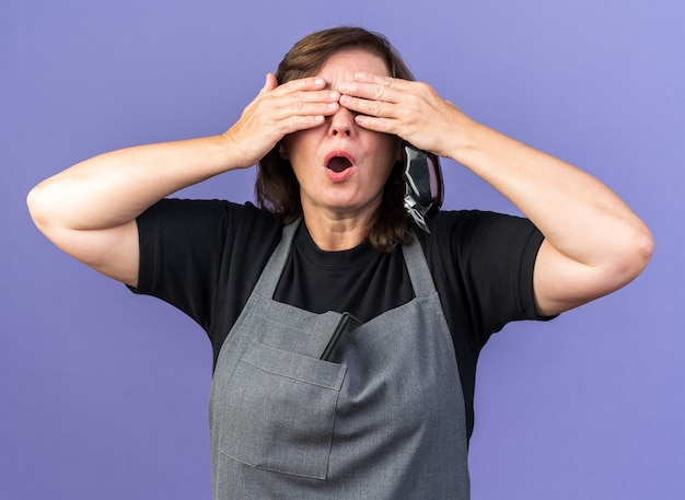 Niespokojna dorosła fryzjerka w mundurze zakrywająca oczy rękami trzymająca maszynkę do strzyżenia włosów odizolowaną na fioletowej ścianie z kopią miejsca