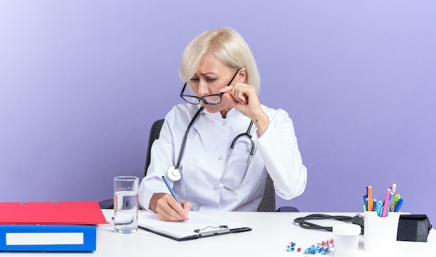 Niespokojna dorosła lekarka w okularach optycznych w szacie medycznej ze stetoskopem siedzi przy biurku z narzędziami biurowymi patrząc na schowek odizolowany na fioletowej ścianie z miejscem na kopię