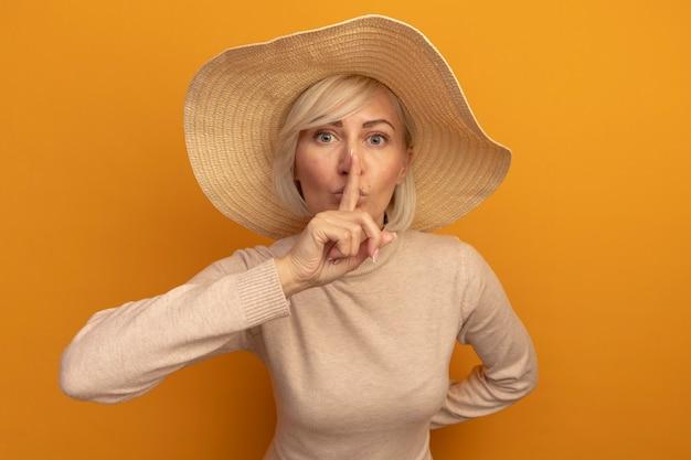 Niespokojna ładna blondynka słowiańska kobieta z plażowym kapeluszem robi gest ciszy na pomarańczowo