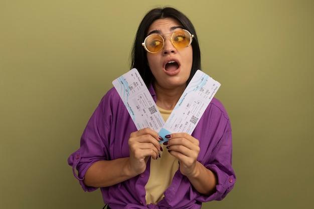 Niespokojna ładna brunetka kobieta w okularach przeciwsłonecznych trzyma bilety lotnicze i patrzy na bok na białym tle na oliwkowej ścianie