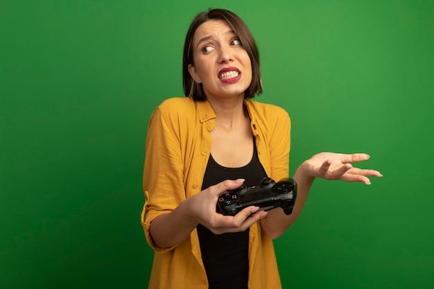 Niespokojna ładna kaukaska kobieta trzyma kontroler gier i trzyma rękę otwartą, patrząc na bok na białym tle