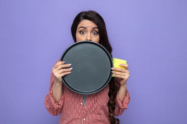Niespokojna ładna kaukaska sprzątaczka trzyma talerz i gąbkę i patrzy