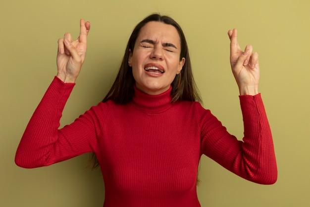 Niespokojna ładna kobieta stoi z zamkniętymi oczami i krzyżuje palce na oliwkowej ścianie