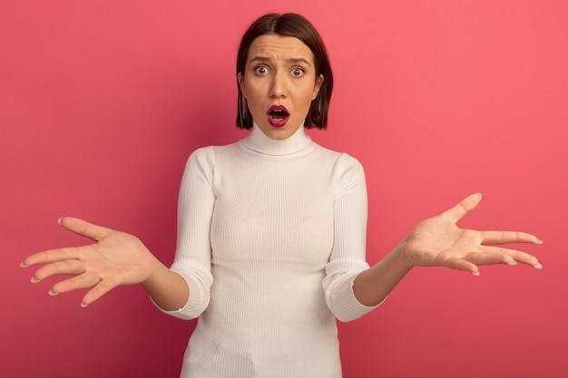 Niespokojna ładna kobieta trzyma ręce otwarte patrząc z przodu na białym tle na różowej ścianie