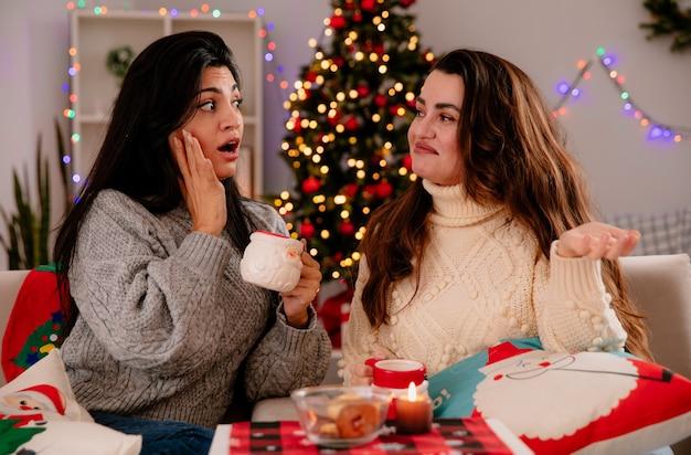 Niespokojna ładna młoda dziewczyna trzyma kubek i patrzy na swojego zdezorientowanego przyjaciela siedzącego na fotelach i cieszącego się świątecznym czasem w domu