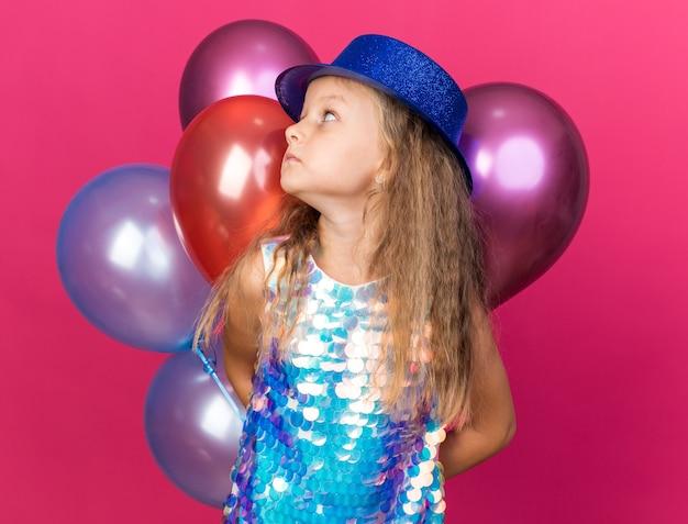 Niespokojna mała blondynka w niebieskim kapeluszu imprezowym trzymająca balony z helem i patrząca na bok odizolowaną na różowej ścianie z miejscem na kopię