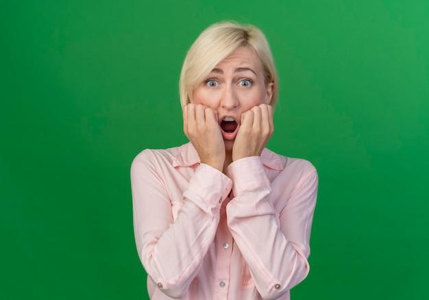 Niespokojna młoda blond słowiańska kobieta kładąc ręce na twarzy na białym tle na zielono z miejsca na kopię