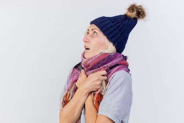 Niespokojna młoda blondynka chora kobieta w czapce zimowej i trzymając szalik patrząc w górę na białym tle na białej ścianie