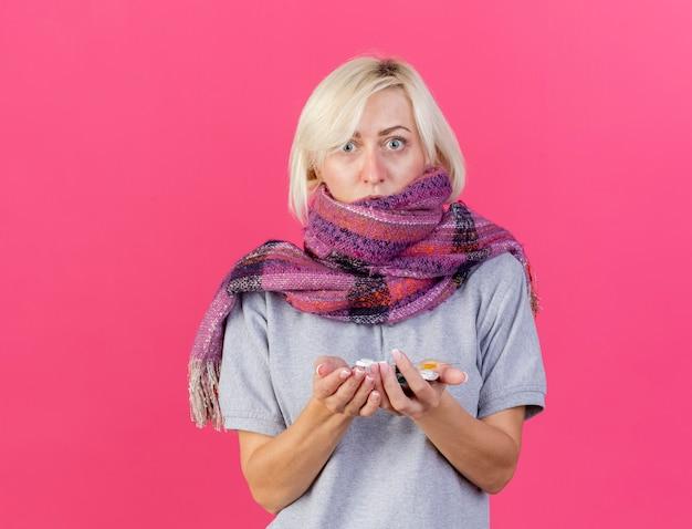 Niespokojna młoda blondynka chora słowiańska chora na sobie szalik trzyma paczki pigułek medycznych