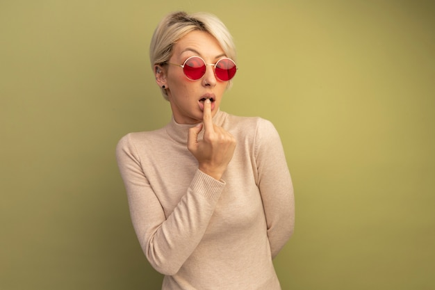 Niespokojna młoda blondynka w okularach przeciwsłonecznych trzymająca rękę za plecami, kładąca palec na wardze
