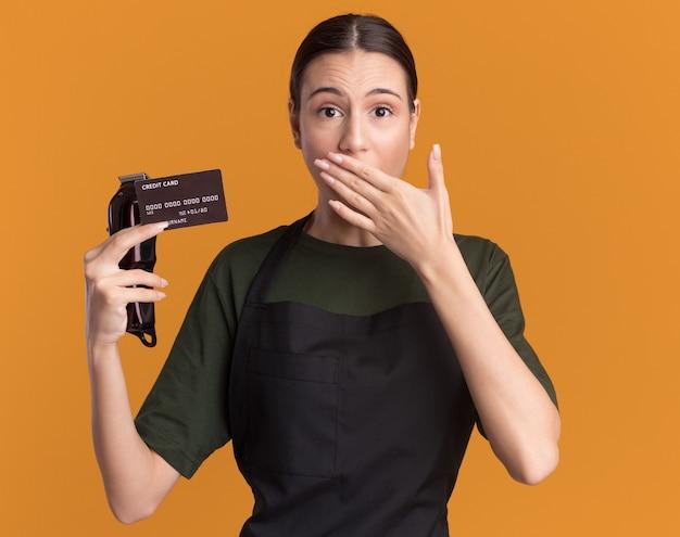 Niespokojna młoda brunetka fryzjer dziewczyna w mundurze trzyma maszynki do strzyżenia włosów i kartę kredytową, kładąc rękę na ustach na białym tle na pomarańczowej ścianie z miejscem na kopię