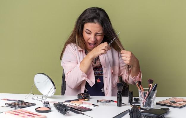 Niespokojna młoda brunetka siedzi przy stole z narzędziami do makijażu, tnąc jej włosy nożyczkami
