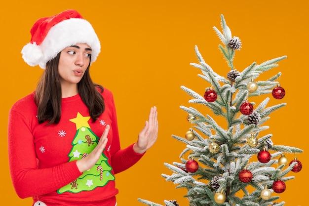 Niespokojna młoda dziewczyna kaukaska z santa hat trzyma ręce otwarte patrząc na choinkę na białym tle na pomarańczowym tle z miejsca na kopię