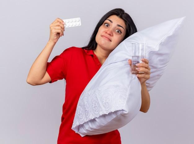 Niespokojna młoda kaukaska chora dziewczyna przytula poduszkę kładąc głowę na niej patrząc na aparat trzymający opakowanie tabletek i szklankę wody na białym tle