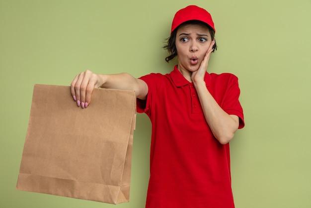 Niespokojna młoda ładna dostawa kobieta kładzie rękę na twarzy i trzyma papierowe opakowanie na żywność