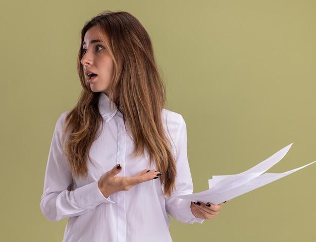 Niespokojna młoda ładna dziewczynka kaukaski trzyma i wskazuje na puste kartki papieru, patrząc z boku na oliwkową zieleń