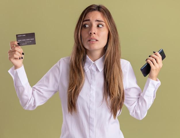 Niespokojna młoda ładna dziewczynka kaukaski trzyma telefon i patrzy na kartę kredytową na oliwkowej zieleni
