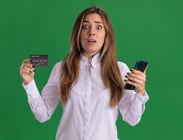 Niespokojna młoda ładna kaukaska dziewczyna trzyma kartę kredytową i telefon na zielonej ścianie z miejscem na kopię