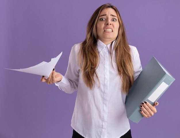 Niespokojna młoda ładna kaukaska dziewczyna trzyma kartki papieru i folder plików