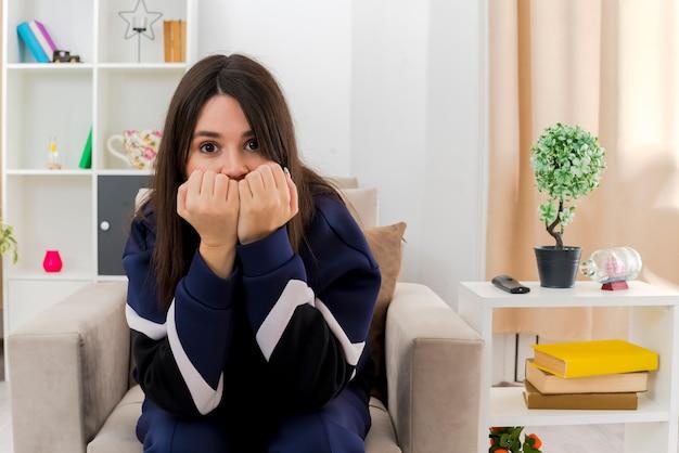 Niespokojna młoda ładna kaukaski kobieta siedzi na fotelu w zaprojektowanym salonie, trzymając pięści na ustach, patrząc