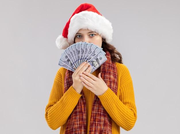 Niespokojna młoda słowiańska dziewczyna z czapką mikołaja iz szalikiem na szyi trzyma pieniądze