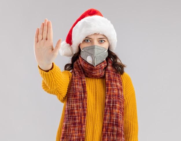Niespokojna młoda słowiańska dziewczyna z czapką świętego mikołaja i szalikiem na szyi, ubrana w maskę medyczną, gestykulując znak stopu na białym tle na białej ścianie z miejscem na kopię