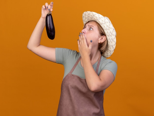 Niespokojna młoda słowiańska ogrodniczka w kapeluszu ogrodniczym kładzie rękę na ustach, trzymając i patrząc na bakłażana