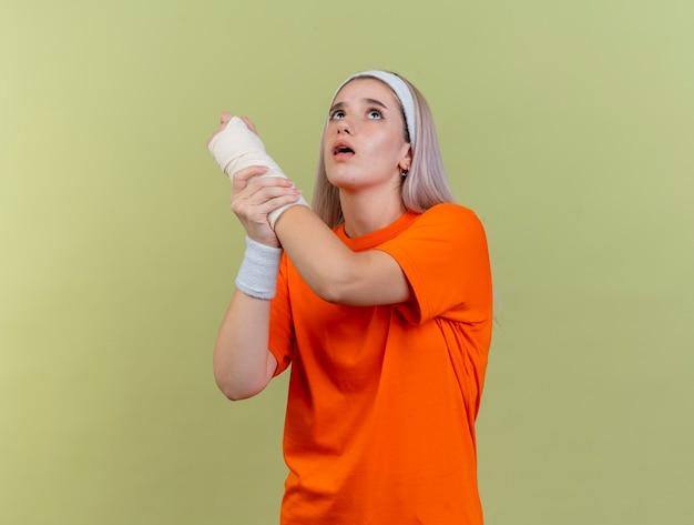 Niespokojna młoda sportowa dziewczyna rasy kaukaskiej z szelkami w opasce i opaskach trzyma rękę, patrząc w górę