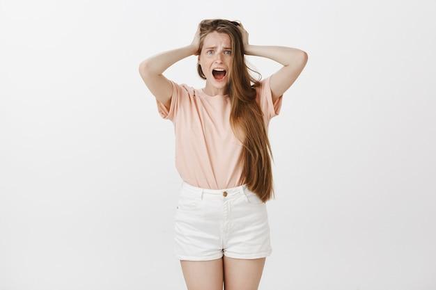 Niespokojna nastolatka pozuje na białej ścianie