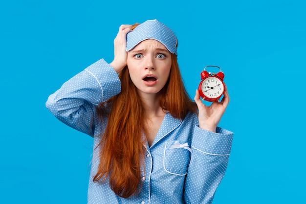 Niespokojna, panikująca młoda rudowłosa przegapiła wywiad, zaspała, trzymając czerwony budzik i dotykając głowy sfrustrowana zaniepokojoną twarzą, nosząc bieliznę nocną i maskę do spania, niebieska ściana