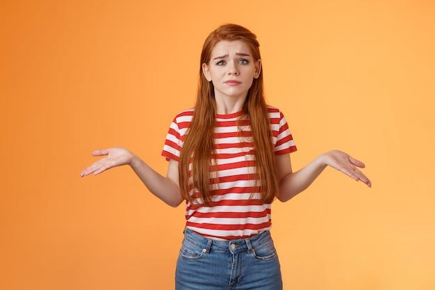 Niespokojna, pytana i nieświadoma urocza, nowoczesna, stylowa rudowłosa kobieta, wzruszając ramionami, rozłożyła ręce na boki u...