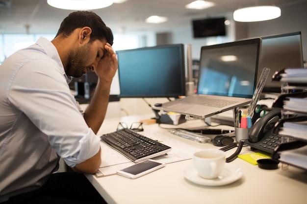 Niespokojny biznesmen siedzi w biurze