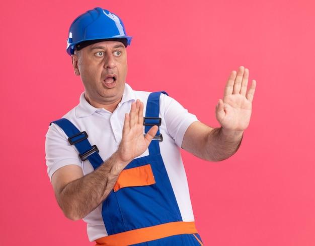 Niespokojny dorosły kaukaski mężczyzna budowniczy w mundurze wyciągając ręce na białym tle