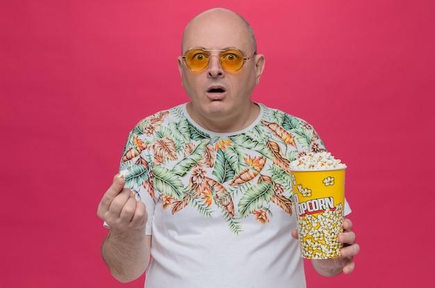 Niespokojny dorosły mężczyzna w okularach przeciwsłonecznych trzymający wiadro popcornu