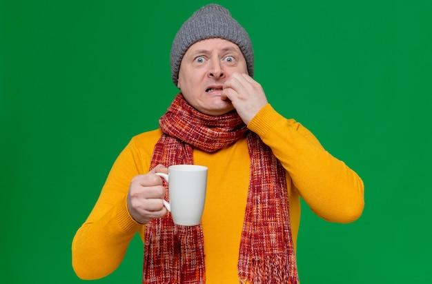 Niespokojny dorosły słowiański mężczyzna w czapce zimowej i szaliku na szyi, trzymający filiżankę i obgryzający paznokcie