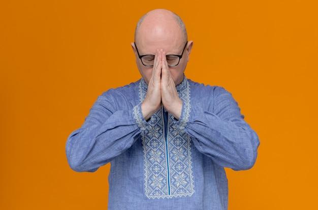 Niespokojny dorosły słowiański mężczyzna w niebieskiej koszuli i w okularach optycznych trzymający ręce razem modląc się