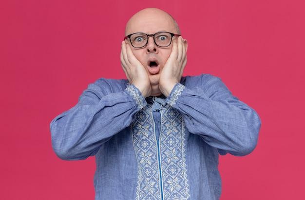 Niespokojny dorosły słowiański mężczyzna w niebieskiej koszuli w okularach kładzie ręce na twarzy i patrzy