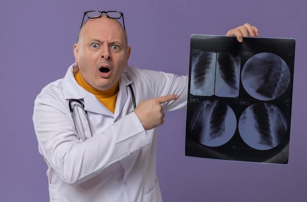 Niespokojny dorosły słowiański mężczyzna w okularach optycznych w mundurze lekarza ze stetoskopem wskazującym na wynik prześwietlenia i patrząc z przodu