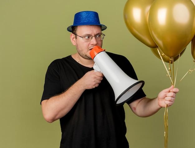 Niespokojny dorosły słowiański mężczyzna w okularach optycznych w niebieskim kapeluszu imprezowym trzyma i patrzy na balony z helem mówiące do głośnika