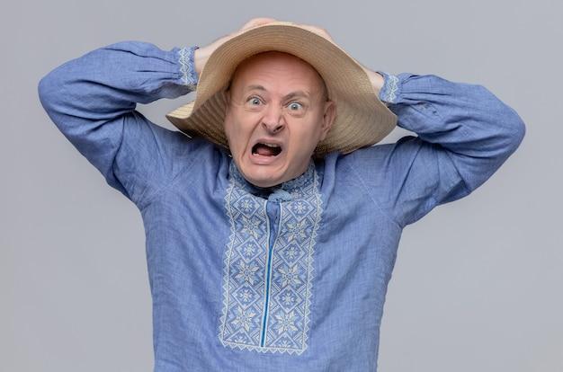 Niespokojny dorosły słowiański mężczyzna w słomkowym kapeluszu i niebieskiej koszuli patrzący z przodu