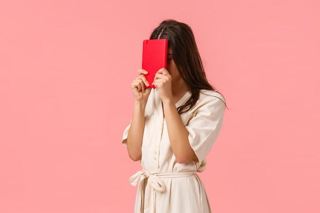 Niespokojny i zmęczony młody pracownik kobiety uderza pięścią w czoło notatnikiem, zamyka oczy