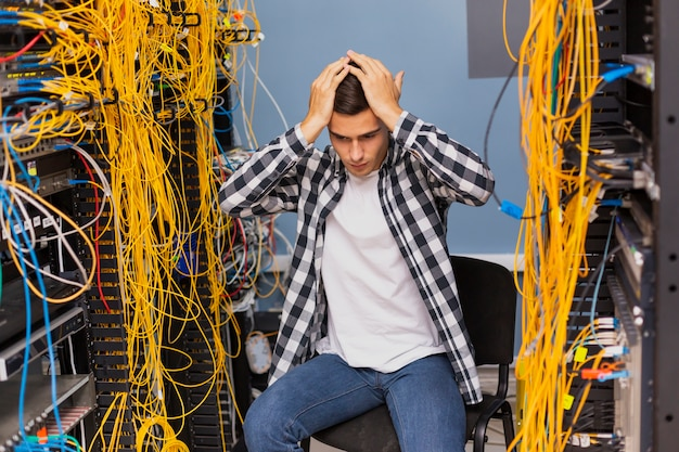 Niespokojny inżynier sieci siedzi na serwerowni