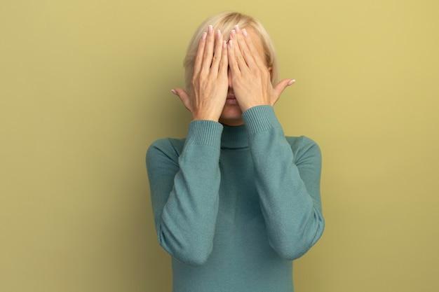 Niespokojny ładna blondynka słowiańska kobieta zakrywa twarz rękami na białym tle