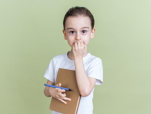 Niespokojny mały chłopiec trzymający książkę i gryzący długopis