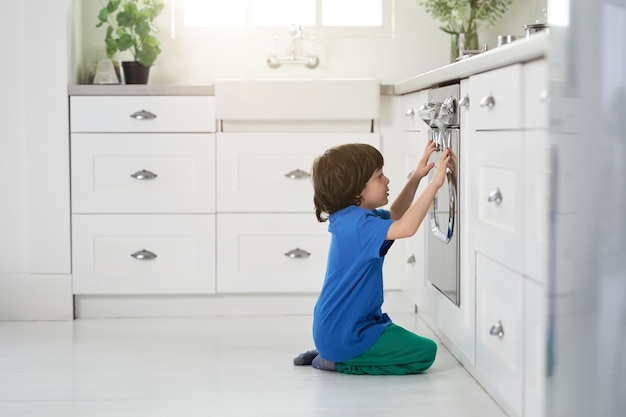 Niespokojny mały latynoski chłopiec ogląda ciasto pieczone w piekarniku, kucając w kuchni. dzieci, koncepcja gotowania. widok z boku