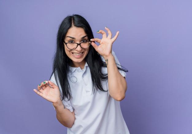 Niespokojny młoda brunetka kaukaski dziewczyna trzyma okulary optyczne i wygląda na białym tle na fioletowej ścianie