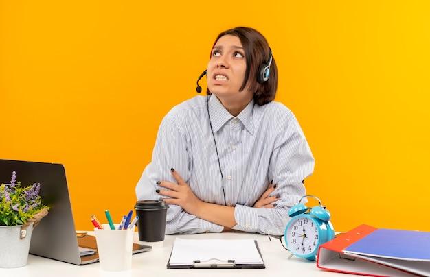 Niespokojny młoda dziewczyna call center sobie zestaw słuchawkowy siedzi z zamkniętą postawą przy biurku patrząc w górę na białym tle na pomarańczowy