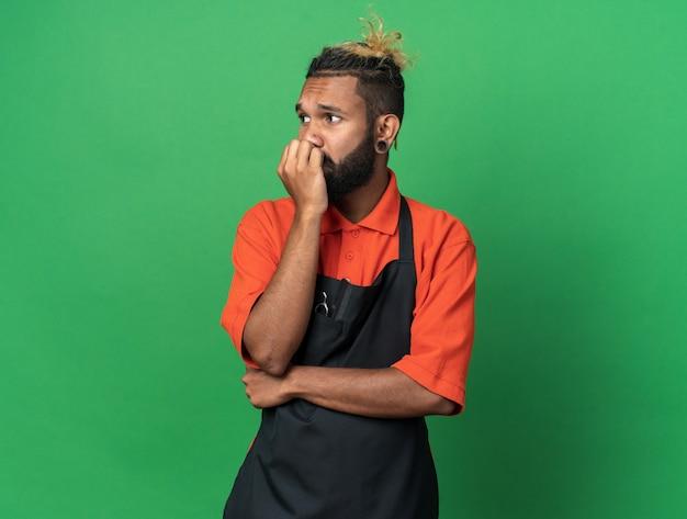 Niespokojny młody afro-amerykański męski fryzjer ubrany w mundur, kładący rękę na ustach, patrzący na bok odizolowany na zielonej ścianie z kopią przestrzeni