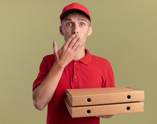 Niespokojny młody blond chłopiec na dostawę kładzie rękę na ustach i trzyma pudełka po pizzy na oliwkowej zieleni